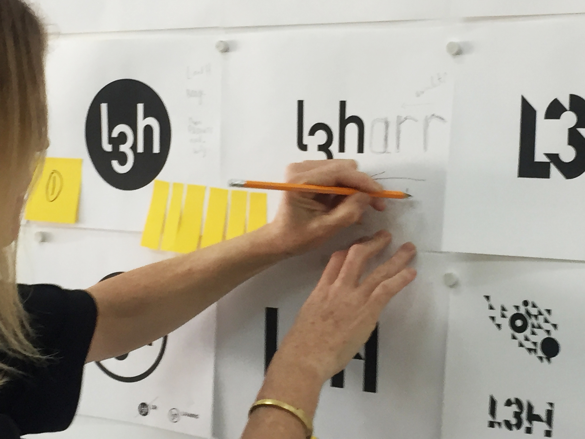 Kat marks up some logos on the wall for L3Harris